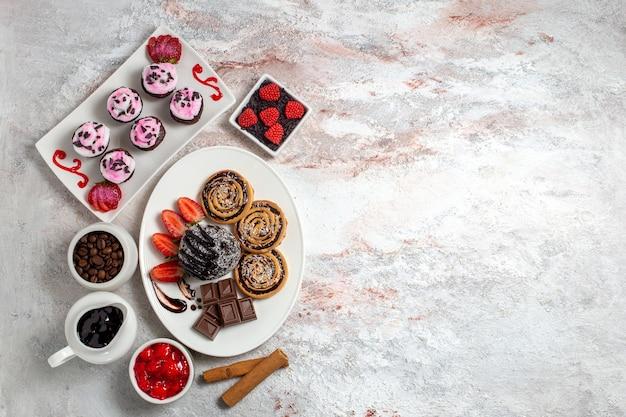 Vista superior de galletas dulces con pastel de chocolate sobre un fondo blanco galleta galleta pastel dulce azúcar té