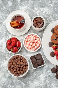 Vista superior galletas fresas y bombones redondos en la placa ovalada cuencos con dulces fresas chocolates cereales y té de anís canela en la mesa gris-blanca