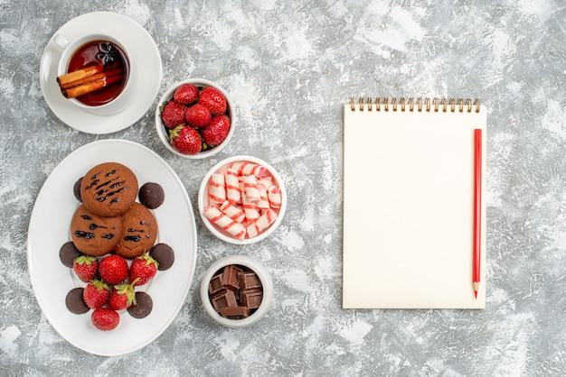 Vista superior de galletas de fresas y bombones redondos en la placa ovalada rodeada de cuencos de dulces fresas chocolates té de canela y lápiz de cuaderno sobre la mesa gris-blanca