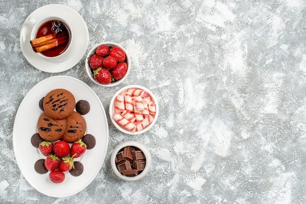 Vista superior galletas fresas y bombones redondos en el plato ovalado rodeado de cuencos de dulces fresas chocolates té de canela en el lado izquierdo de la mesa gris-blanca