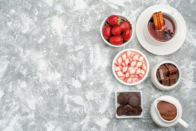 Vista superior galletas fresas cacao y chocolates y té con canela en el lado derecho de la mesa gris-blanca