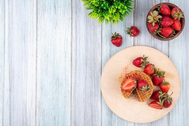 Vista superior de galletas de gofres y fresas en la tabla de cortar y en un recipiente y en la superficie de madera