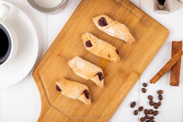 Vista superior de las galletas de harina con mermelada de fresa sobre una plancha de madera sobre fondo blanco.