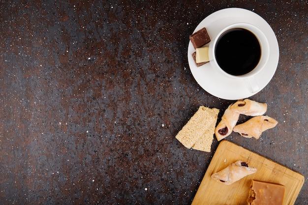 Vista superior de galletas de harina con mermelada de fresa en una tabla de madera y trozos de sésamo kozinaki y una taza de café sobre fondo negro con espacio de copia