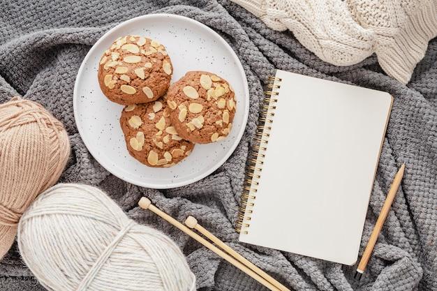 Vista superior de galletas, hilo y agenda en manta