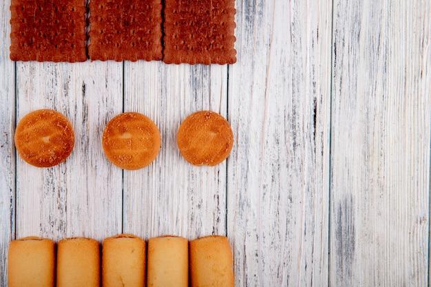 Vista superior galletas con mermelada y galletas de chocolate a la izquierda con espacio de copia sobre fondo blanco de madera