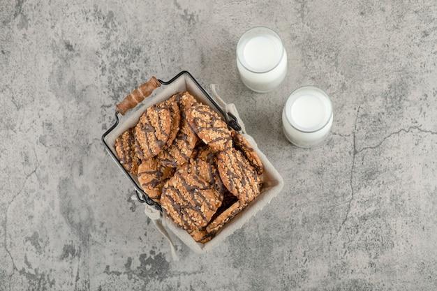 Vista superior de galletas multicereales con glaseado de chocolate en canasta con dos frascos de vidrio de leche.