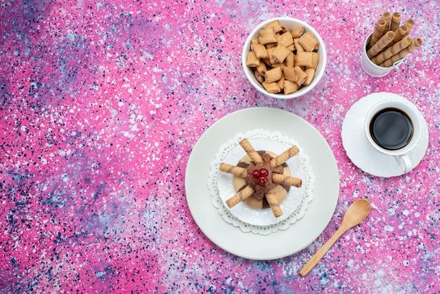 Vista superior de galletas y pastel junto con una taza de café en el fondo de color pastel azúcar café dulce