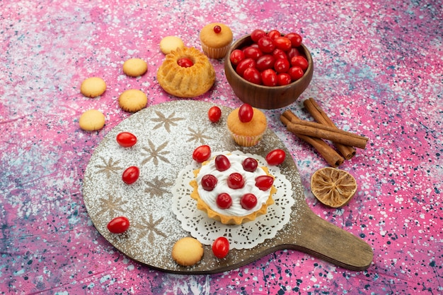 Vista superior de galletas y pasteles con crema y arándanos rojos frescos en la superficie púrpura