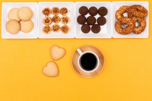 Vista superior de galletas en platos cuadrados y una taza de café sobre superficie amarilla