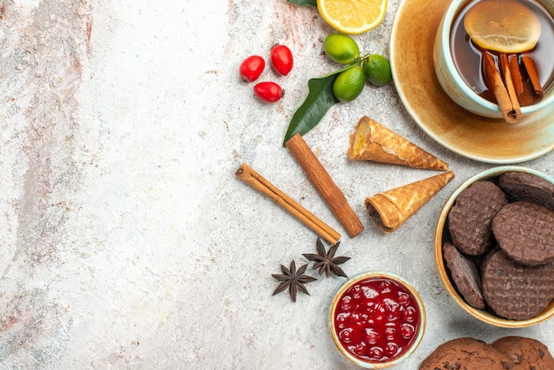 Vista superior de las galletas una taza de té con limón canela en rama cítricos mermelada de anís estrellado
