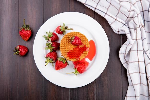 Vista superior de galletas waffle y fresas en placa con tela escocesa sobre superficie de madera