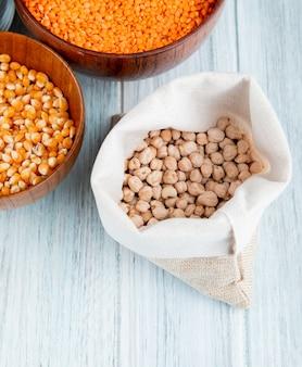 Vista superior de garbanzos secos en una tela de saco y semillas de maíz con lentejas rojas en cuencos de madera sobre mesa rústica