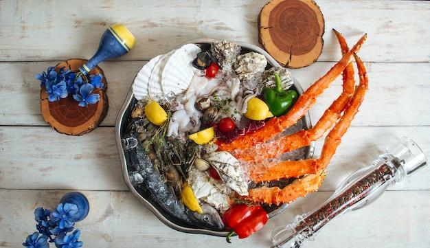 Vista superior de garras de cangrejo fresco con hielo y verduras en un recipiente de metal sobre una mesa de madera blanca