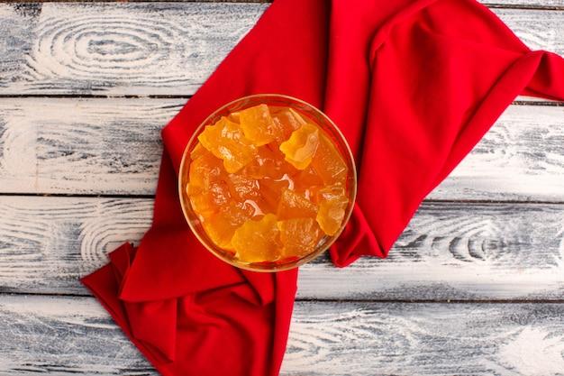Vista superior de gelatinas de naranja dentro del vidrio sobre la superficie rústica gris