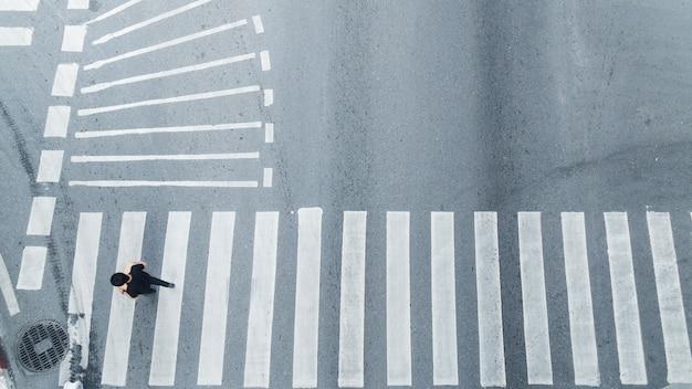 La vista superior de la gente camina en el cruce peatonal de la calle en la calle de la ciudad.