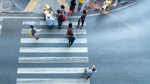 Vista superior de la gente cruza la carretera con señalización. concepto peatones pasando por un paso de peatones.