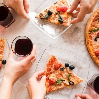 Vista superior gente tomando pizza y vino