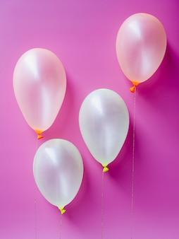 Vista superior globos blancos sobre fondo rosa