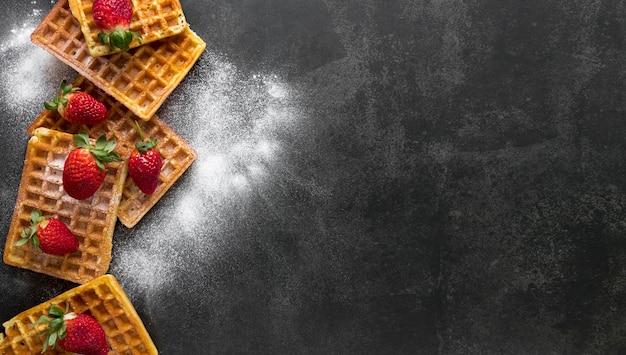 Vista superior de gofres con azúcar en polvo y fresas