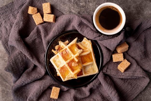 Vista superior de gofres cubiertos de miel con taza de café