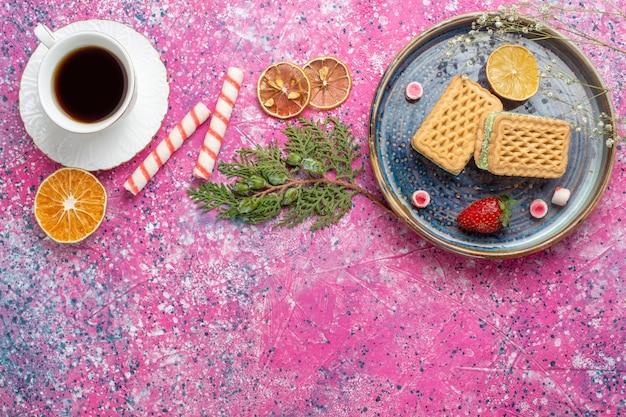 Vista superior de gofres dulces con taza de té en la superficie de color rosa claro