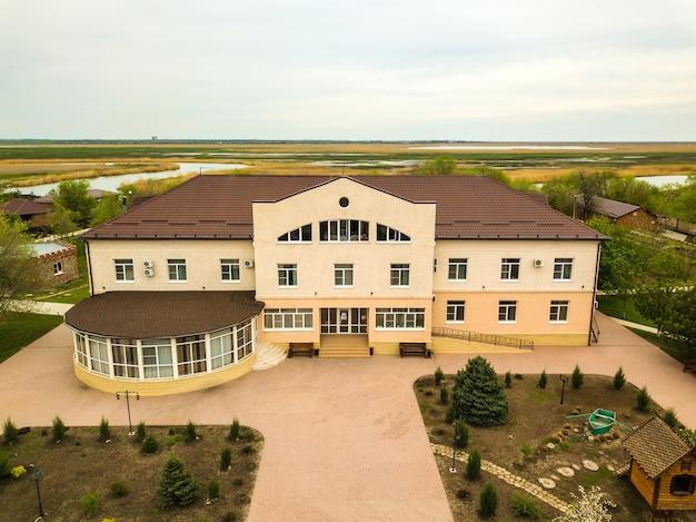 Vista superior gran casa de campo u hotel junto al río.