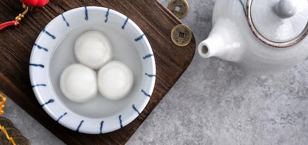 Vista superior del gran tangyuan yuanxiao (bolas de bola de masa de arroz glutinoso) para la comida del festival del año nuevo lunar, las palabras en la moneda de oro significan el nombre de la dinastía que hizo.