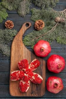 Vista superior de la granada de lejos a bordo de la granada pilled roja en la tabla de cortar junto a tres granadas maduras y ramas de abeto con conos en la mesa