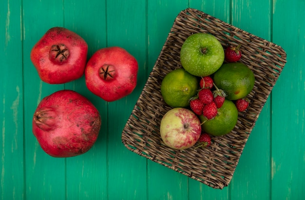 Vista superior de granadas con mandarinas manzanas y fresas en una canasta sobre una pared verde