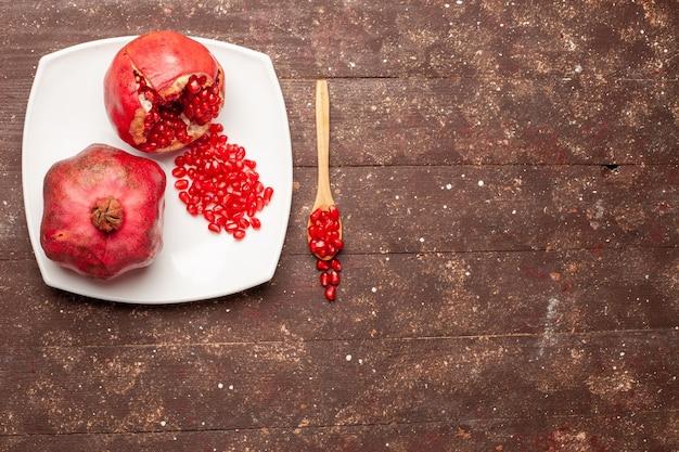 Vista superior granadas rojas frescas dentro de la placa en el escritorio rústico marrón