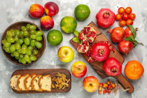Vista superior de granadas rojas frescas con pastel de mandarinas y manzanas en el escritorio blanco claro