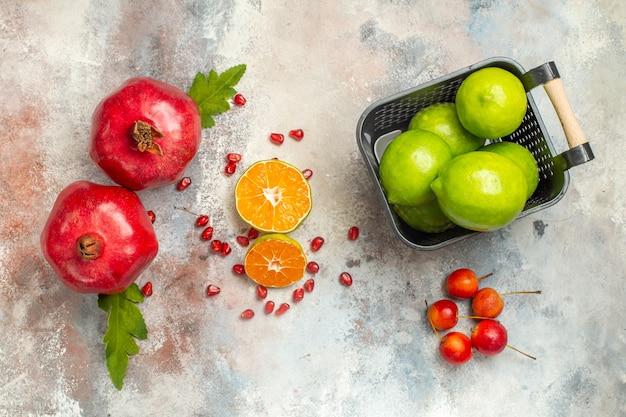 Vista superior granadas rojas rodajas de limón limones en un tazón de manzanas celestiales en superficie desnuda