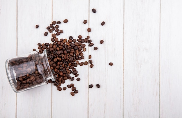Vista superior de los granos de café cayendo de un frasco de vidrio sobre un fondo de madera blanca con espacio de copia