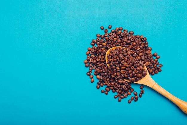 Vista superior de granos de café en cuchara de madera