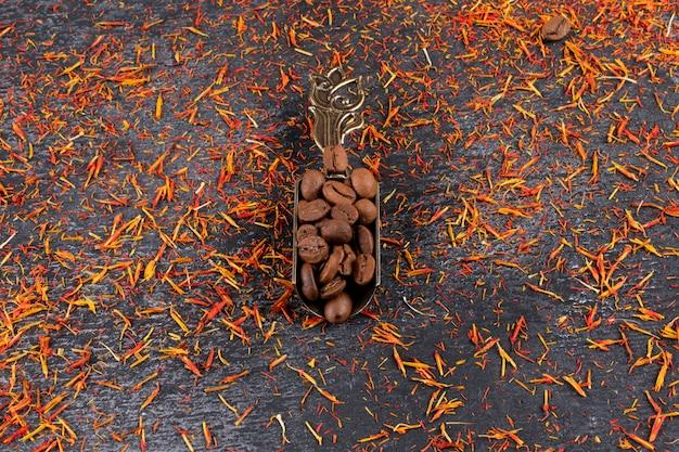 Vista superior de granos de café en una cuchara sobre superficie picante