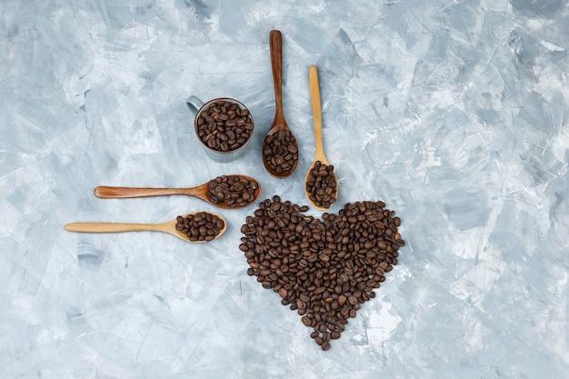 Vista superior de los granos de café en cucharas de madera y taza sobre fondo de yeso gris. horizontal