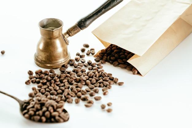 Vista superior de granos de café esparcidos alrededor, una bolsa de cartón, una esponja y una cafetera rústica