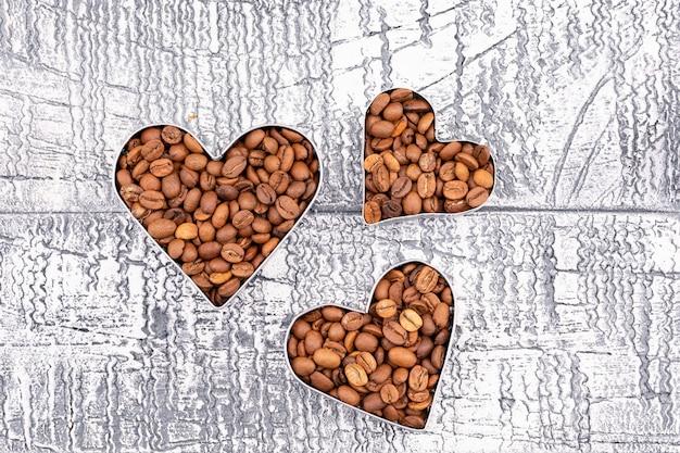 Vista superior de granos de café en forma de corazón en superficie retro