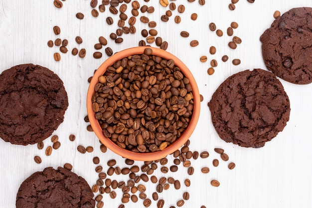 Vista superior de granos de café y galletas de chocolate sobre superficie blanca