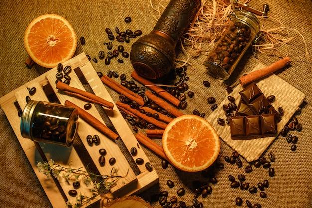 Vista superior de granos de café con molinillo de café chocolate naranja y caja de madera