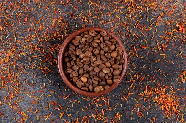 Vista superior de granos de café en placa sobre superficie picante
