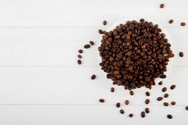Vista superior de granos de café en un plato sobre fondo blanco con espacio de copia