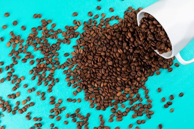 Vista superior de granos de café con taza sobre superficie azul