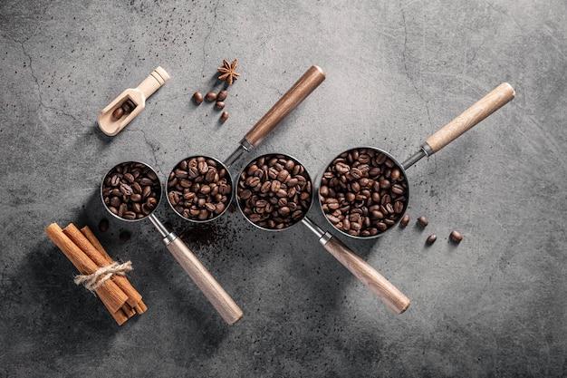Vista superior de los granos de café en tazas con pala y palitos de canela