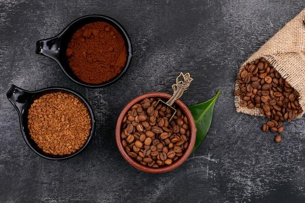 Vista superior de granos de café en un tazón de cerámica y café instantáneo sobre superficie negra