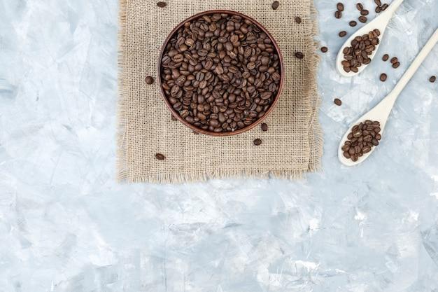 Vista superior de los granos de café en un tazón y cucharas de madera sobre yeso y un pedazo de fondo de saco. horizontal