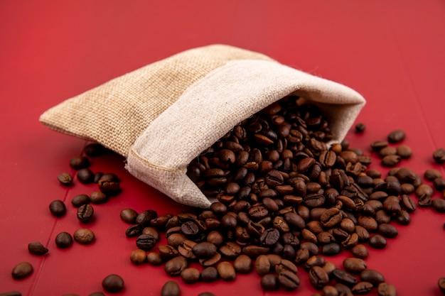 Vista superior de los granos de café tostados cayendo de una bolsa de arpillera sobre un fondo rojo.