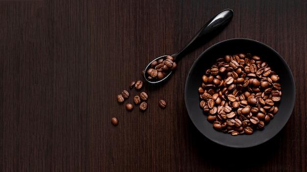 Vista superior de granos de café tostados con cuchara y espacio de copia