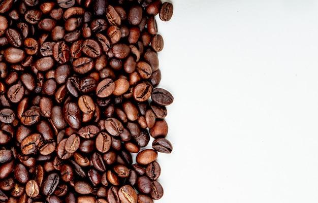 Vista superior de granos de café tostados esparcidos sobre fondo blanco con espacio de copia